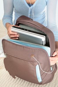 A notebook being inserted into the Belkin Laptop Sling Bag