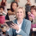 Jane Lynch holding her Nook and smiling.