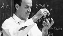 A black and white picture of Richard Feynman in front of a blackboard