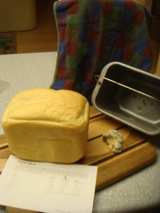 A loaf of bread with recipe and baking pan from a bread machine