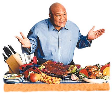 George Foreman displaying all the foods the Grand Champ Grill can be used to cook.