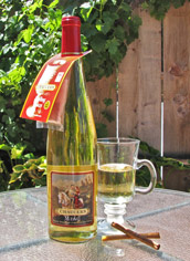 A bottle of Chaucer's Mead and a mug half filled with the wine upon an outdoor table